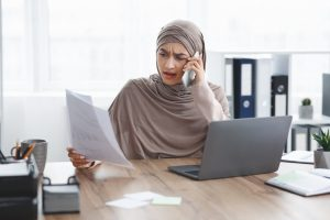 Stressed muslim businesswoman checking documentation and talking on cellphone in office